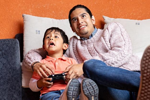 Jovem sentado com uma criança pequena em um sofá enquanto os dois jogam videogame