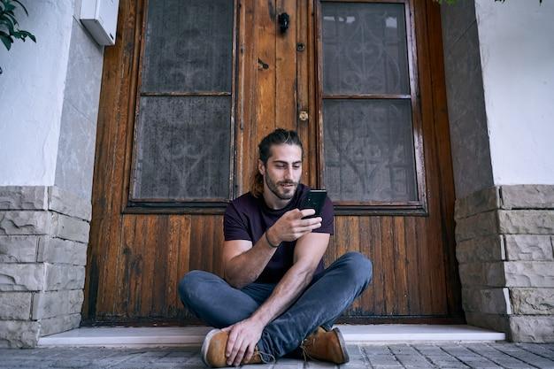 Jovem sentado em frente a uma porta de madeira marrom, fazendo uma ligação comercial