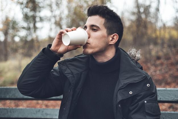 Jovem sentado em um banco, segurando o copo de café descartável no parque na temporada de outono.