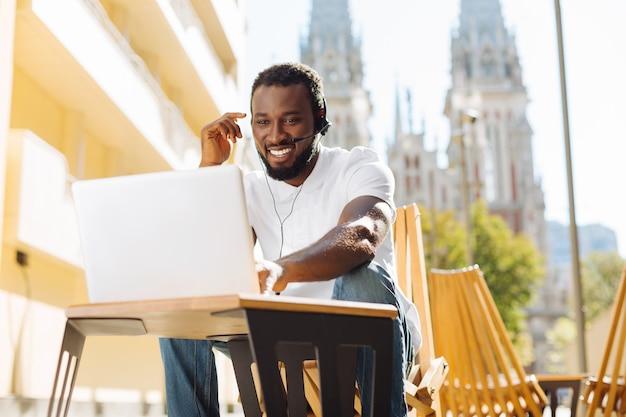 Jovem sentado em um terraço lendo um artigo