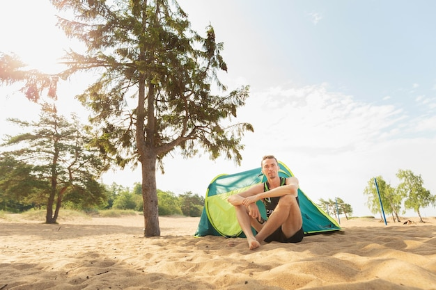 Jovem sentado em uma barraca posando de formiga