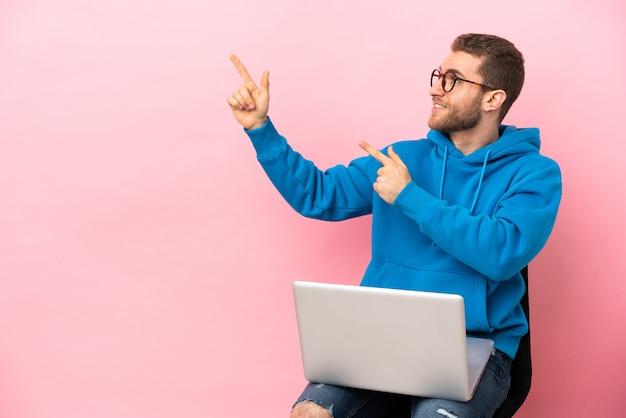 Jovem sentado em uma cadeira com laptop apontando com o dedo indicador uma ótima ideia