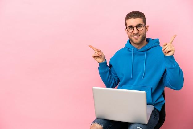 Jovem sentado em uma cadeira com laptop apontando o dedo para as laterais e feliz
