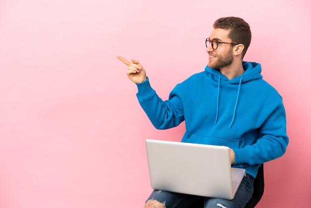 Jovem sentado em uma cadeira com laptop apontando o dedo para o lado e apresentando um produto