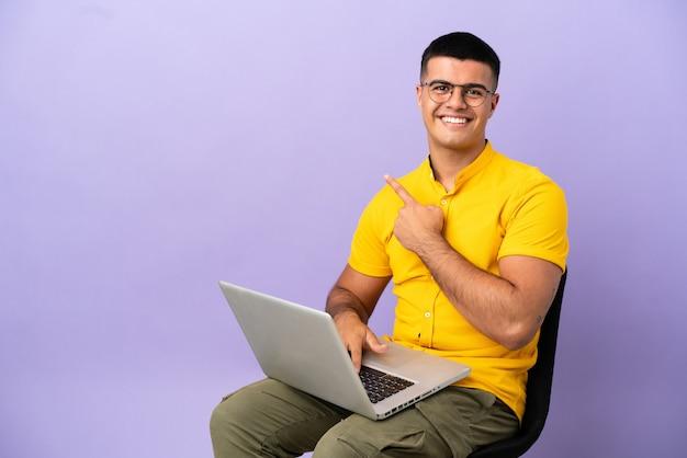 Jovem sentado em uma cadeira com laptop apontando para o lado para apresentar um produto