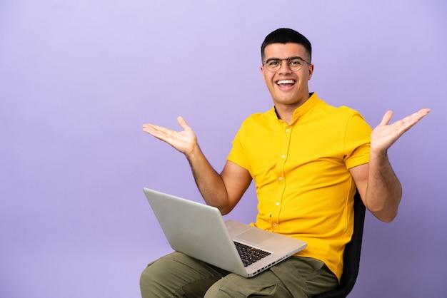 Jovem sentado em uma cadeira com laptop com expressão facial chocada
