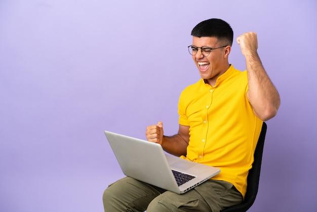 Jovem sentado em uma cadeira com laptop comemorando uma vitória