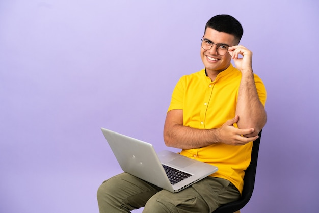 Jovem sentado em uma cadeira com laptop de óculos e feliz