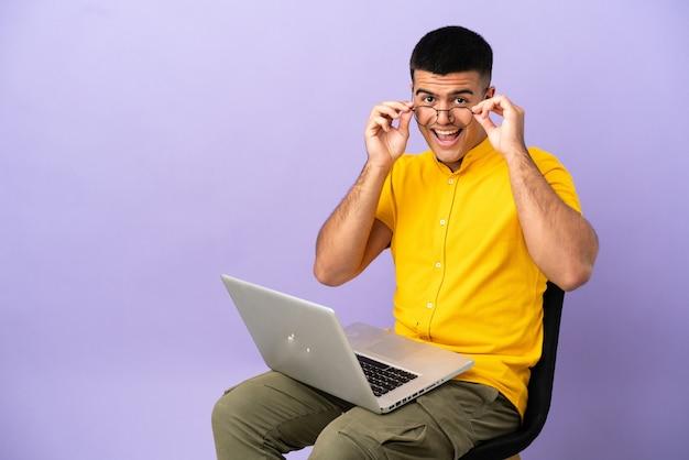 Jovem sentado em uma cadeira com laptop de óculos e surpreso