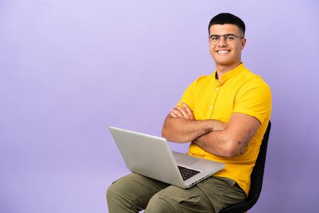 Jovem sentado em uma cadeira com laptop, mantendo os braços cruzados na posição frontal