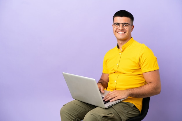 Jovem sentado em uma cadeira com laptop rindo