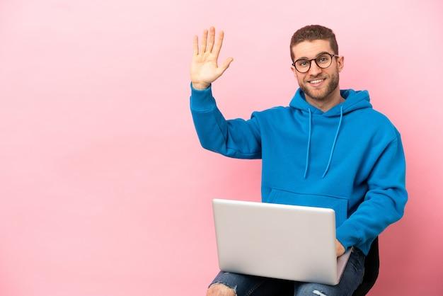 Jovem sentado em uma cadeira com laptop saudando com a mão com expressão feliz