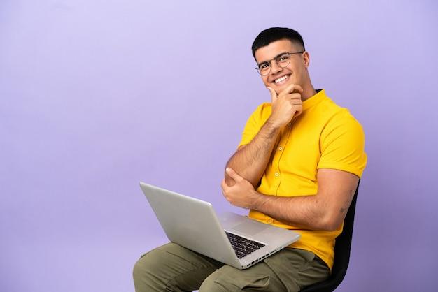 Jovem sentado em uma cadeira com laptop sorrindo