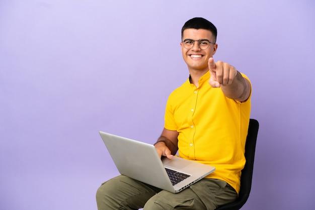 Jovem sentado em uma cadeira com o laptop apontando o dedo para você com uma expressão confiante