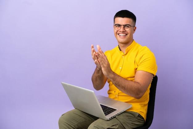Jovem sentado em uma cadeira com um laptop aplaudindo após uma apresentação em uma conferência