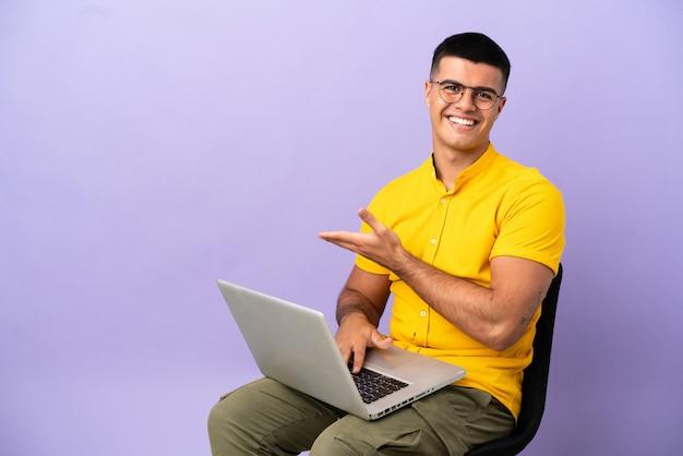 Jovem sentado em uma cadeira com um laptop apresentando uma ideia enquanto olha sorrindo para