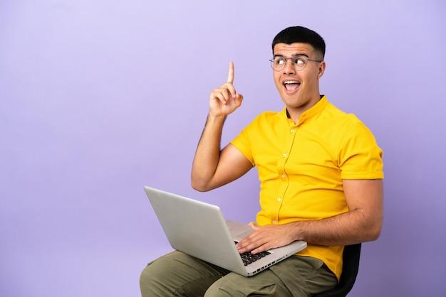 Jovem sentado em uma cadeira com um laptop com a intenção de descobrir a solução enquanto levanta um dedo