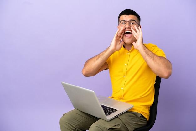 Jovem sentado em uma cadeira com um laptop gritando e anunciando algo