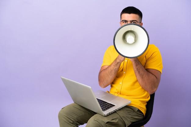 Jovem sentado em uma cadeira com um laptop gritando no megafone
