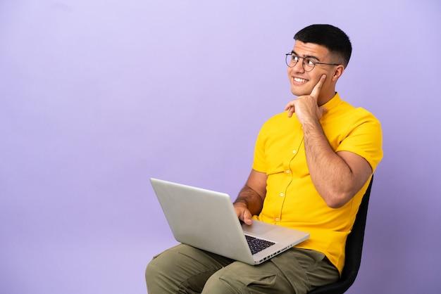 Jovem sentado em uma cadeira com um laptop pensando em uma ideia enquanto olha para cima