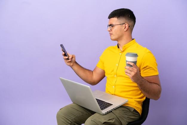 Jovem sentado em uma cadeira com um laptop segurando um café para levar e um celular