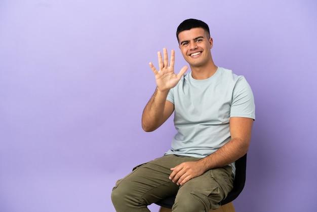 Jovem sentado em uma cadeira sobre um fundo isolado, contando cinco com os dedos