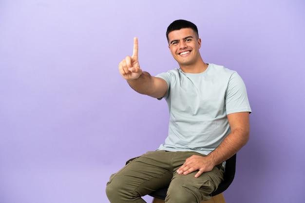 Jovem sentado em uma cadeira sobre um fundo isolado, mostrando e levantando um dedo