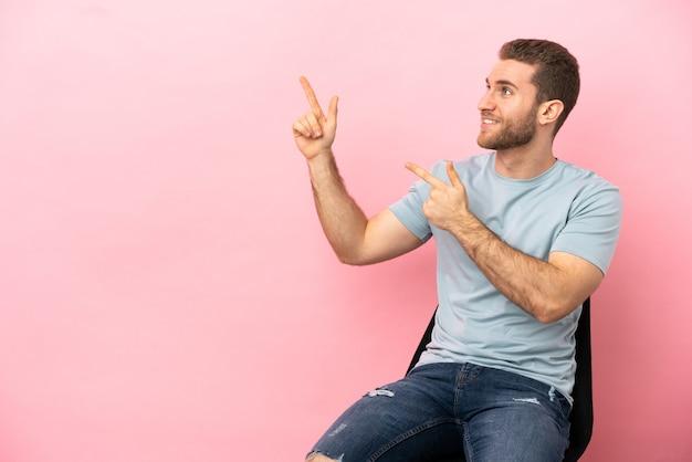 Jovem sentado em uma cadeira sobre um fundo rosa isolado apontando com o dedo indicador uma ótima ideia