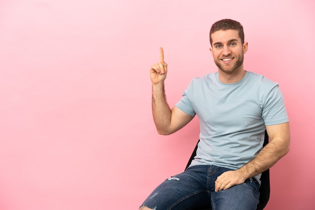 Jovem sentado em uma cadeira sobre um fundo rosa isolado apontando para uma ótima ideia