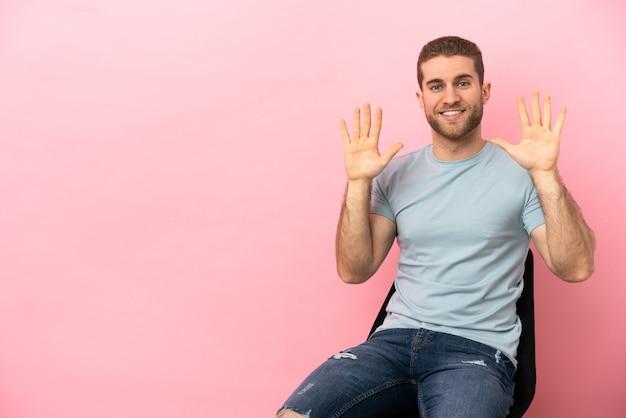 Jovem sentado em uma cadeira sobre um fundo rosa isolado, contando dez com os dedos