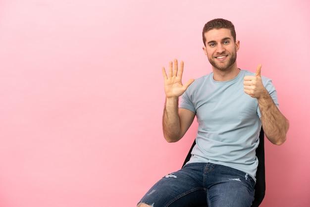 Jovem sentado em uma cadeira sobre um fundo rosa isolado, contando seis com os dedos
