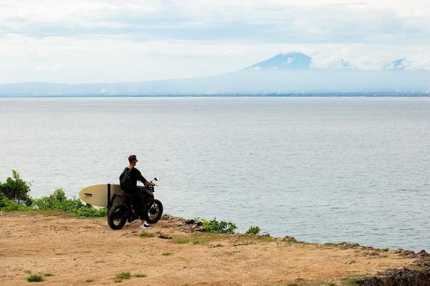 Jovem sentado em uma motocicleta com uma prancha de surf