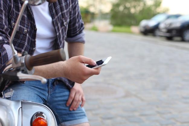 Jovem sentado em uma scooter e usando um telefone inteligente
