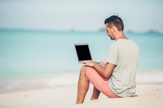 Jovem sentado na areia com o laptop na praia do caribe tropical. homem com computador e trabalhando na praia