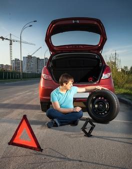 Jovem sentado na estrada encostado em um carro quebrado