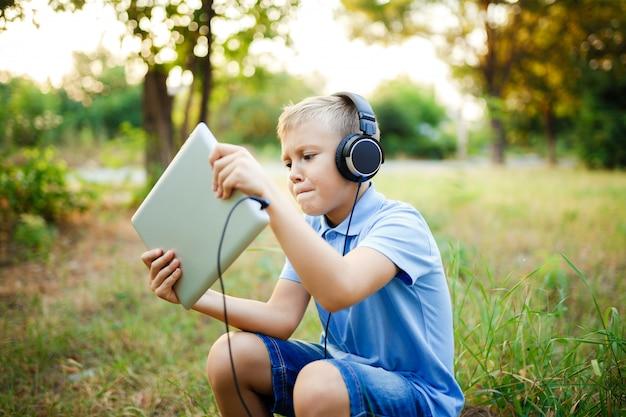 Jovem sentado na floresta usando fones de ouvido e jogando um jogo no tablet pc.
