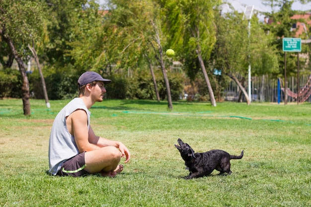 Jovem sentado na grama e cachorro preto olhando para a bola de tênis no ar proprietário masculino brincando com animal de estimação