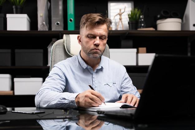 Jovem sentado na mesa do computador e faz anotações no diário