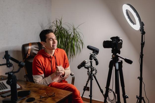 Jovem sentado na mesa falando para a câmera. cara gravando um vídeo com equipamentos profissionais. vlog, conceito freelancer.