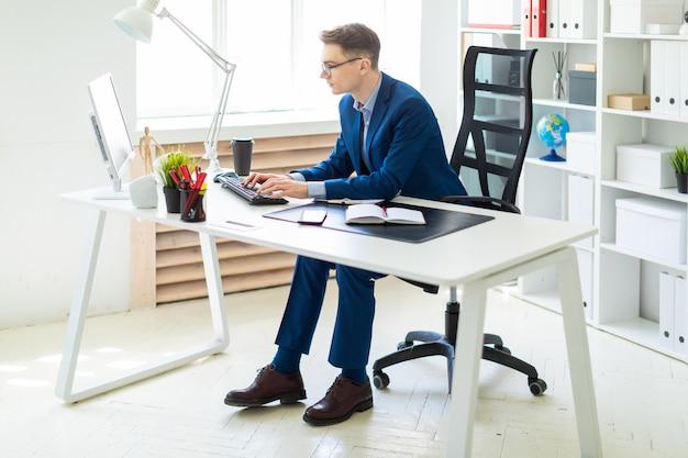 Jovem sentado na mesa no escritório e trabalhando no computador.