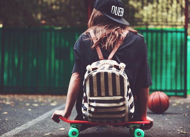 Jovem sentado na prancheta de plástico laranja centavo no asfalto na tampa