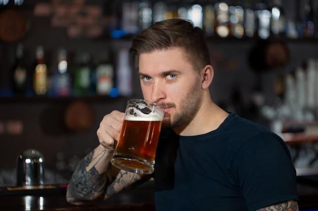 Jovem sentado no balcão de bar com uma caneca de cerveja light