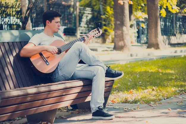 Jovem sentado no banco do parque tocando violão com o capo