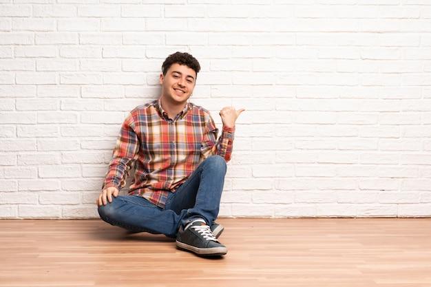 Jovem sentado no chão, apontando para o lado para apresentar um produto
