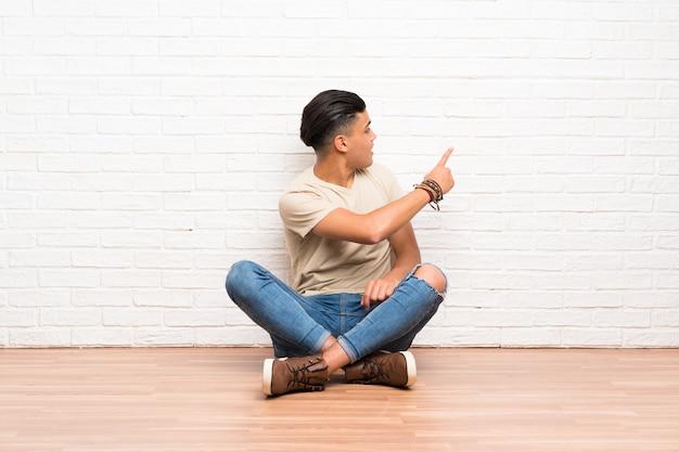 Jovem sentado no chão apontando para trás com o dedo indicador