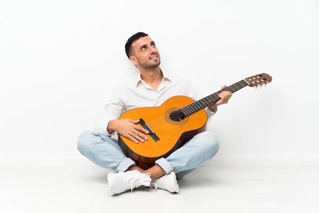 Jovem sentado no chão com a guitarra, olhando para cima enquanto sorrindo