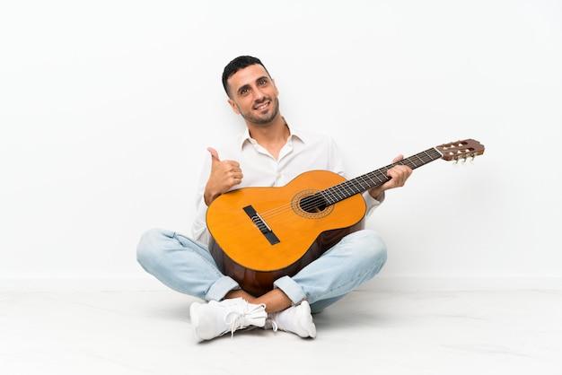Jovem sentado no chão com guitarra com polegares para cima, porque algo de bom aconteceu