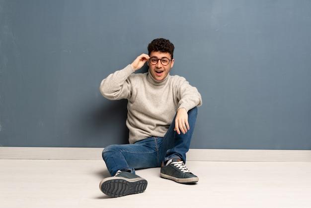 Jovem sentado no chão com óculos e surpreso