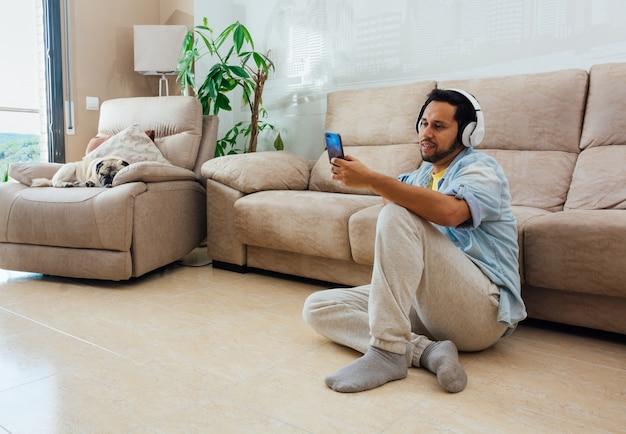 Jovem sentado no chão com telefone e fones de ouvido