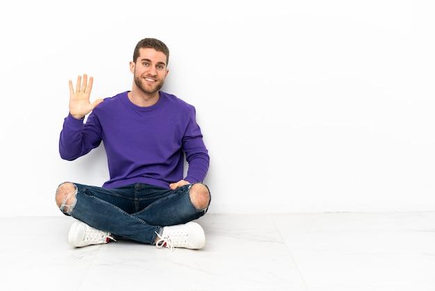 Jovem sentado no chão contando cinco com os dedos